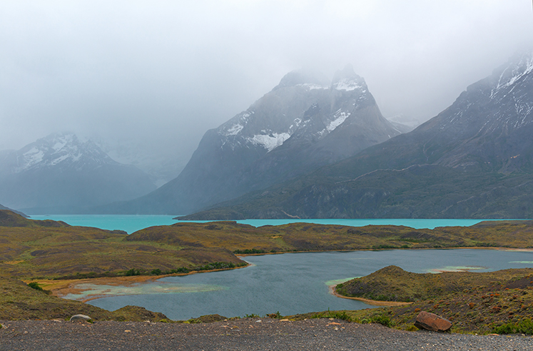 The turquoise colored Nodernskjold lake and the Cuernos del Paine in the fog, located in the Torres del Paine national park near Puerto Natales, Patagonia, Chile.